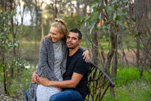 Couple Outdoors Sitting On Park Bench In Bush With Eucalyptus Trees