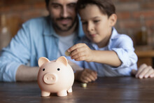 Crop Close Up Of Family Putting Coin Into Pink Piggy Bank, Caring Father Teaching Little Son Kid To Save Money For Future, Sitting At Wooden Table At Home, Insurance And Investment Concept