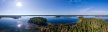 Aerial Panorama Of A Large Dark Blue Lake That Is Surrounded By Trees. The Sun Is In The Photo.