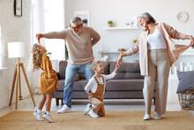 Active Senior Grandparents Dancing With Two Happy Kids Grandchildren In Living Room