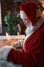 Serious Santa Claus In Red Cap And Glasses Sitting At Wooden Table With Burning Candles And Reading Letter