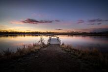 Sunrise Over A Dock On A Pond