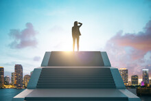 Back View Of Young European Businesswoman Standing On Top Of Stairs On Bright City Background With Sky View. Leadership, Growth And Success Concept.