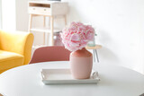 Vase with hydrangea flowers on table in living room