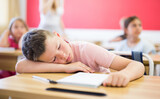 Tired little boy lying on work desk put head on his hand, feel exhausted with hard learning process