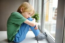 Sad Little Boy Is Sitting Near Window And Watching Street. Lonely At Home. No Friends, No Siblings. One Baby In Family. Bad Relations With Parents. Upset Offended Kid.
