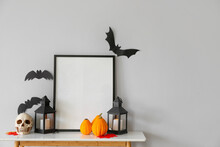 Blank Frame With Halloween Decorations On Table Near Light Wall
