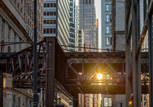 In Chicago, The Sun Shines Brightly Through Space In The Train Tracks Of The Famous L Or Elevated Train, Downtown In The Loop.