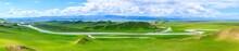 Bayinbuluke Grassland Natural Scenery In Xinjiang,China.The Winding River Is On The Green Grassland.Panoramic View.