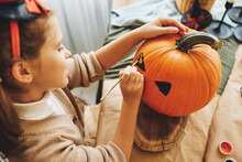 Little Kid Girl Making Jack-o-lantern While Preparing For Halloween Party At Home