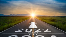 New Year 2022 Or Start Straight Concept.word 2022 Written On The Road In The Middle Of Asphalt Road At Sunset.Concept Of Planning And Challenge Or Career Path,business Strategy,opportunity And Change