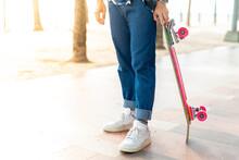 An Asian Man's Legs Are Standing. Stand Holding A Surf Skate On The Beach Walkway Of Bangsaen. Thailand