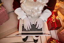 Santa Claus Sitting At His Home And Reading Email On Laptop With сhristmas Requesting Or Wish List Near The Fireplace And Tree With Gifts. New Year And Merry Christmas , Happy Holidays Concept
