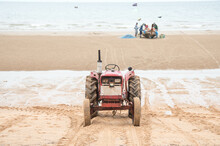 Tractors Waiting To Haul A Local Fishing Boat Out Of The Sea At Low Tide At Jomtien Beach, Pattaya, Thailand