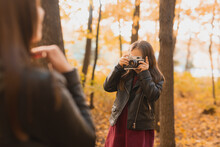 Child Girl Photographer Takes Pictures Of A Mother In The Park In Autumn. Hobbies, Photo Art And Leisure Concept.