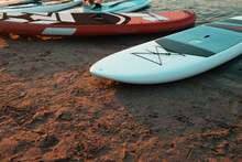 Three Sup Boards Lying Near The Water On Sea On The Sunset. Healthy Lifestyle.