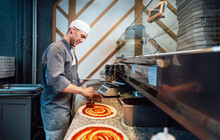A Glad Chef Spreads The Sauce On The Pizza Dough. Catering Kitchen Work.