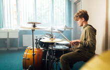 Boy Musician Behind A Drum Kit.
