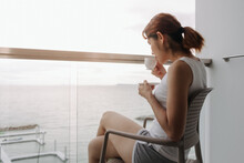 Asian Woman Drink Coffee And Relax On The Balcony With Sea View.