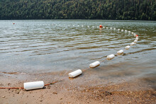 A Strip Of White Buoys Partially Overlooking The Sandy Shore. Buoys Enclose A Safe Area For Bathers