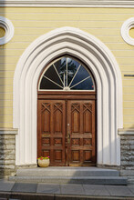 Wooden Door Over White Stone Arch And Flower Pot.