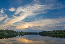 A Picturesque Landscape With A Sunset Sky Reflected In A Pond. Forest On The Horizon. Sunset Over The Lake.