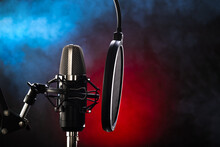 Studio Microphone And Pop Filter On Red-blue Background. Minimalism. There Are No People In The Photo. Close-up. Recording Studio, Vocals. Music, Concert, Purity Of Sound, Debate.