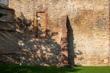 Tan Color European  Medieval Stone Wall Background, With View Of A Former Window Frame And Supporting Column In Bright Sunlight