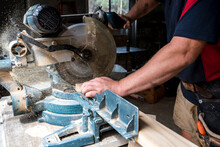 Man Cutting Timber With Drop Saw With Sawdust Coming Out Of Saw