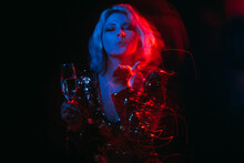 Festive Magic. Inspired Woman. Holiday Wish. Night Club Party. Happy Misterious Lady Sending Blow Kiss With Glass Champagne Long Exposure Red Blue Neon Light Motion Blur On Black.