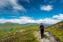 Along The West Highland Way. A Lonely Hiker Walks On The Hiking Path In The Highland Moor