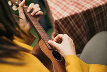 Girl With Dreadlocks Closeup Playing An Acoustic Instrument Ukulele In Autumn On The Terrace
