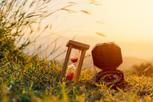 Hourglass And Compass With Sunrise In The Morning At Mountain