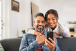Happy indian couple using smartphone at home
