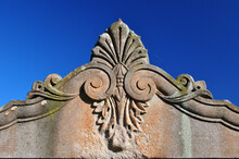 Decorative Stone Carving On Old Headstone Seen Against Blue Sky