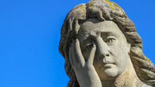 A Stone Monument To A Woman With An Extremely Sad And Tragic Expression