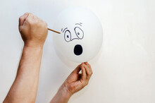 A Balloon With A Face Painted On It And A Rusty Nail. Man Holding White Balloon And Large Sharp Nail. Hand Drawn Emotion Of Surprise, Outrage. Indoors.