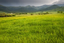 Idyllic And Peaceful Landscape In The Countryside. Lush Grass In The Foreground And Misty Mountains In The Distance As A Background
