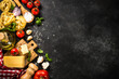 Italian food background black table. Raw Pasta, fresh tomatoes, olive oil, parmesan, spices and basil. Top view with copy space.