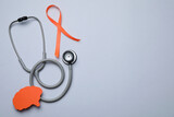 Fototapeta Kawa jest smaczna - Orange ribbon, stethoscope and paper brain cutout on light grey background, flat lay with space for text. Multiple sclerosis awareness