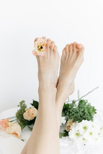 Women's Legs In Fresh Colors.  Summer Lifestyle Portrait Of The Legs Of An Attractive Girl With Wild Flower Buds Between Her Fingers. I Enjoy Life, Nature. The Legs Are In Focus, The Flowers Are Blurr
