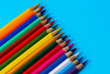 Set Of Wooden Colored Pencils On A Blue Sheet Of Paper Background