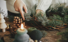 Woman Hands Holding Fir Branch And Arranging Christmas Wreath On Rustic Wooden Background With Candle, Pine Cones, Thread. Festive Workshop. Making Rustic Christmas Wreath Close Up