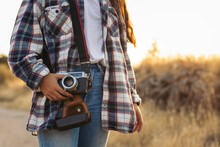 Faceless Photographer With Retro Photo Camera And Case In Countryside