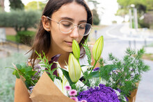 Crop Concentrated Woman Smelling Blooming Flower Bouquet In Park