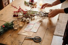 Person Working On Festive Christmas Bouquet On Table