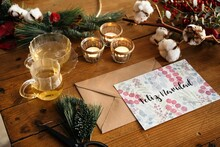 Festive Christmas Composition With Colorful Postcard Against Wooden Background