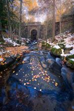 Stone Bridge Over Calm River In Autumn Forest