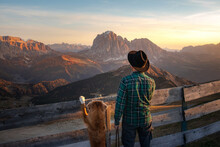A Man With Dog Looking At The Mountains. Dolomites Alps. Hiking, Relax. Nova Scotia Duck Tolling Retriever