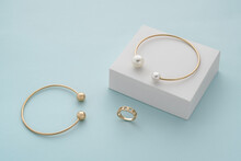 Golden With Pearls Bracelet On White Box And Gold Bracelet And Ring With Copy Space